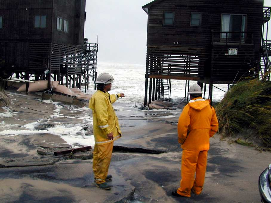 Nags Head, N.C., 8/1/99 -- Ocean overwashes flushed between coastal homes, ripping up their roadways. The change of direction by Dennis brought high seas and winds that battered and flooded the coastal road. Here, crew from NC Power(L) and Virginia Power(R) check the threat of live lines leading to the homes. Photo by DAVE GATLEY/FEMA News Photo  Photo by Dave Gatley - Jul 31, 1999 - Location: Nags Head, NC