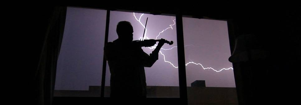 Electric violin... May 23rd, 2013 in a hotel room in Lubbock TX, I was practicing on my ( non-electric ) violin while there was a thunderstorm producing quite some lightning... so I put up the videocam, hoping to catch a video-still of me playing violin with some lightning in the background. I like this inparticular because it almost looks like the lightning comes out of the instrument. Originally shot in FHD 1080p, this videostill is cropped for even larger wide-screen drama. For the record, I was playing a few notes from the soundtrack of 'Last of the Mohicans'... but I'm really not a good violinist