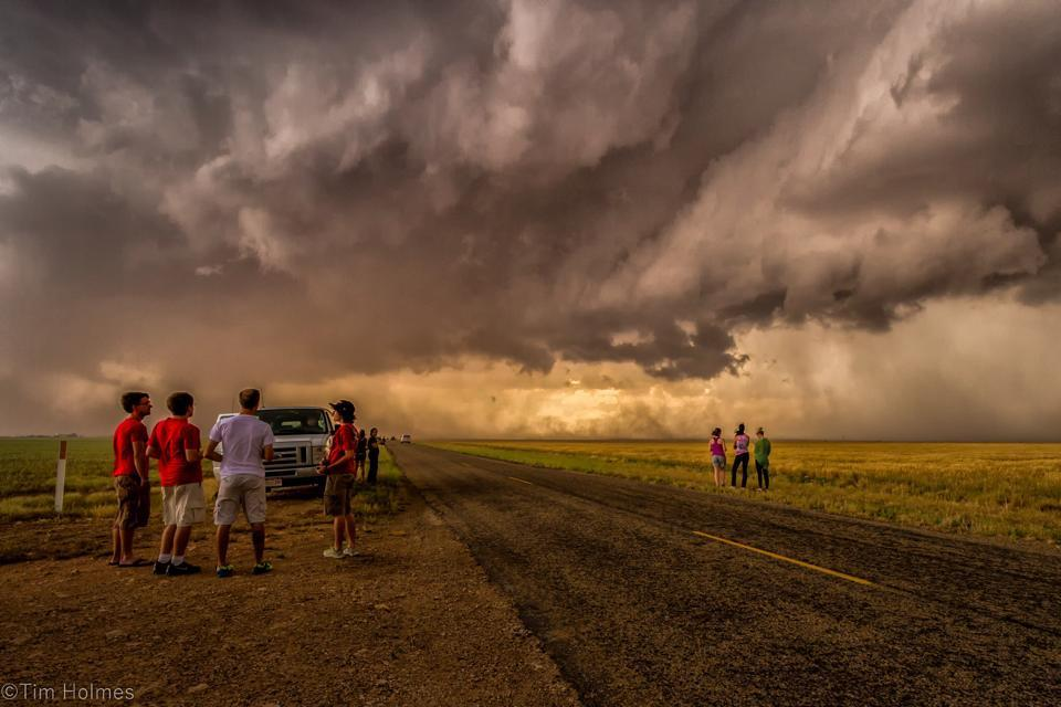 Chasers watching a swirling supercell pass overhead.