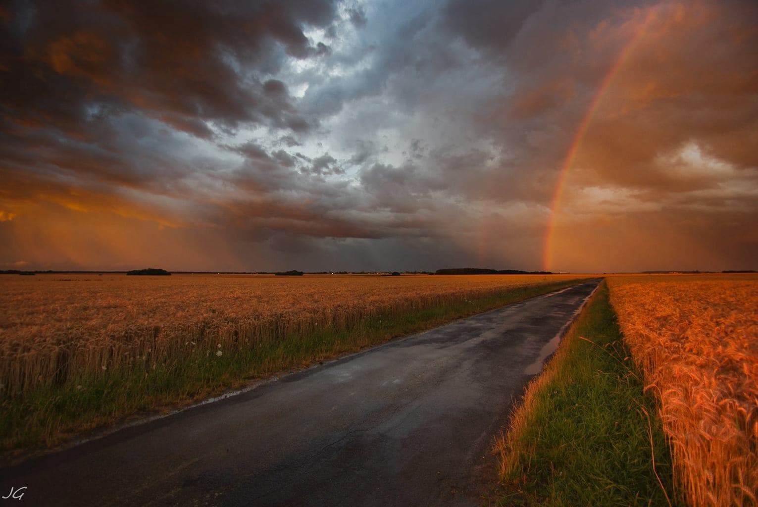 Beautiful sunset behind a strong thunderstorm, a rainbow and showers above weathfield. Central plain of France.