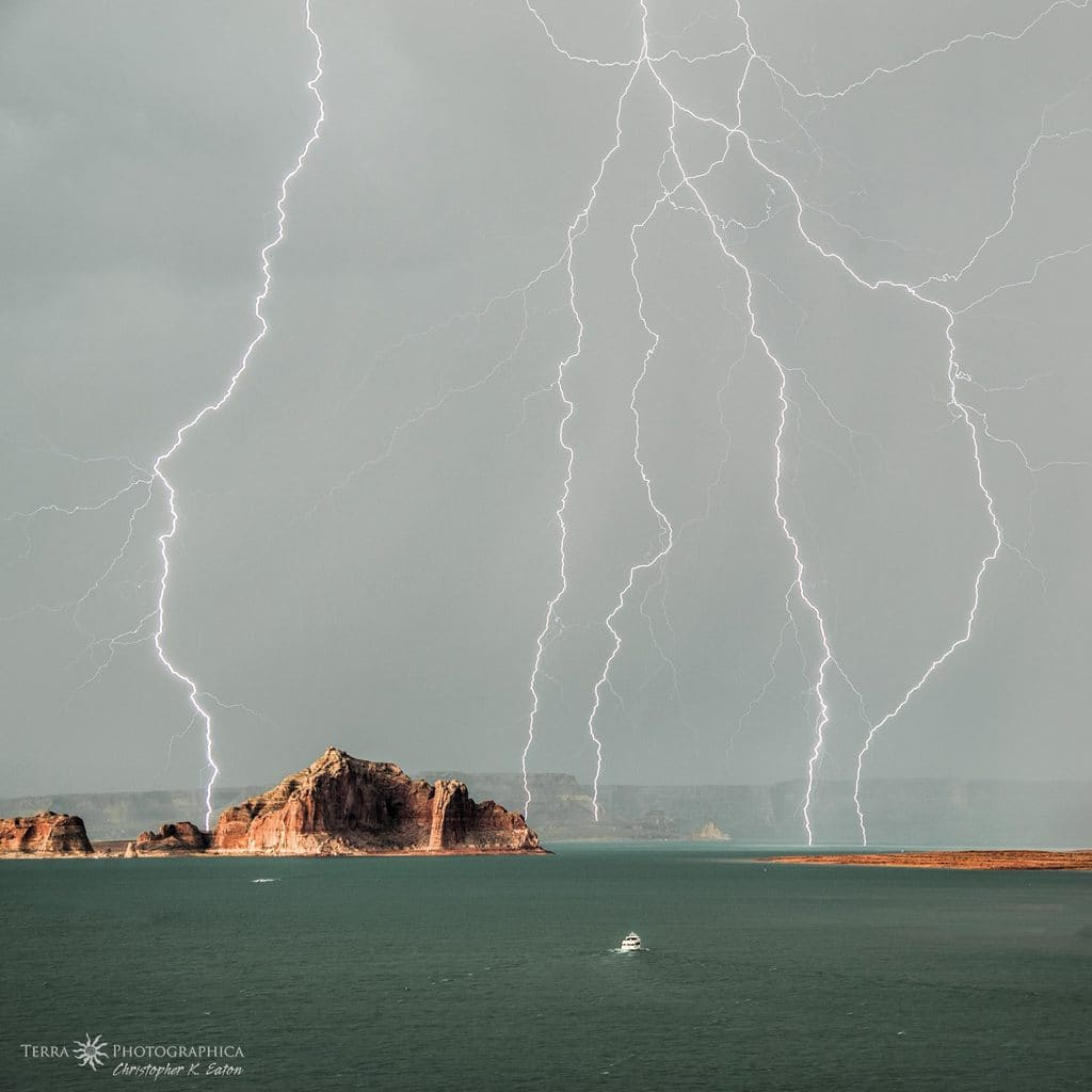 """""""Front Row Seat"""" - A tour boat stops to enjoy the show of a monsoon storm unleashing a barrage of lightning over Lake Powell in Glen Canyon National Recreation Area."""