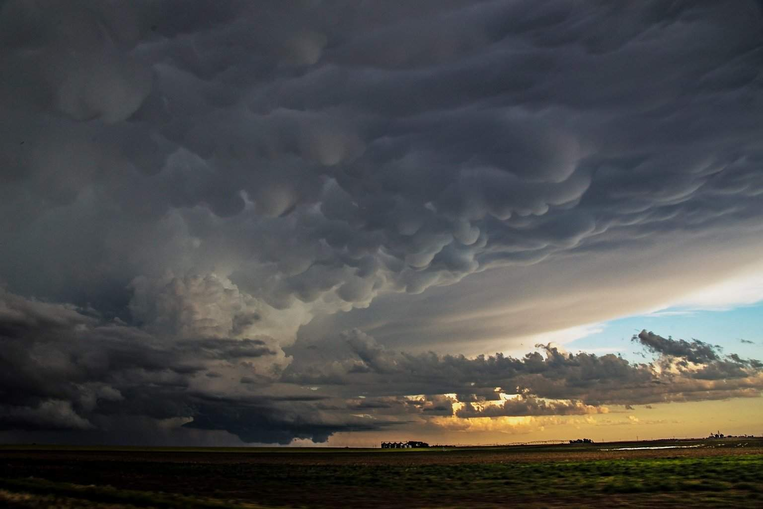 Tail end of Plains/Ensign KS supercell shortly after birth 5-24-2015 Mammatus stretches from underneath the anvil above a sturdy updraft and wall cloud as the sun sets on this amazing storm. It would go on to produce multiple tornadoes that we experienced later in the night, from a large wedge, stovepipe, elephant trunk and cone shapes all making appearances. Difficult shot here in diminishing light from a moving vehicle.