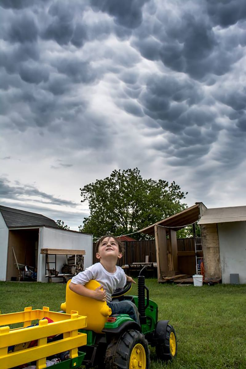"I normally don't share pictures publicly of my boy, but he has become fascinated with weather. He watches the weather channel, is always on Radarscope on my phone, and loves watching the clouds and lightning. We had some crazy mammatus clouds before some bad weather moved through DFW a few weeks ago. He was stopped on his ""tractor"" outside just looking at them."
