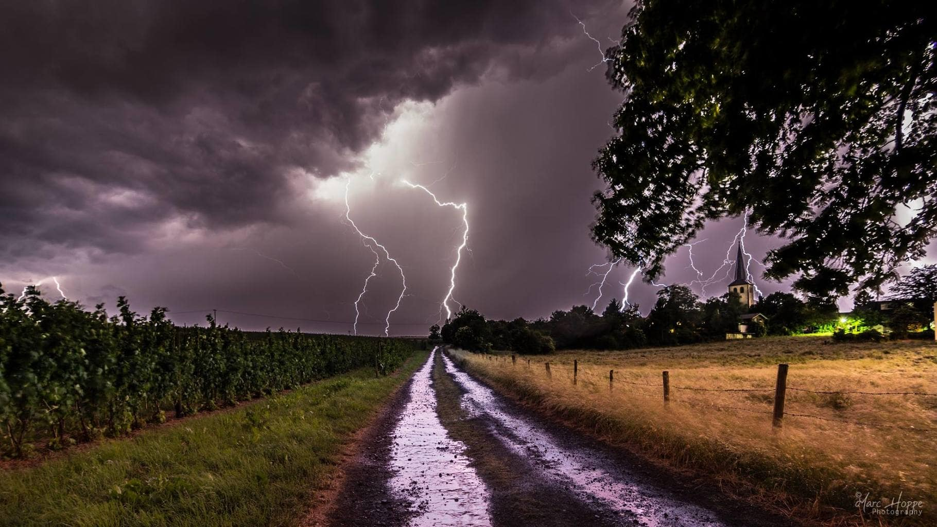 Multiple lightning strikes behind a little town near Bonn, Germany - 06-06-2015 To bad I didn't catch the big lightning behind the tree.