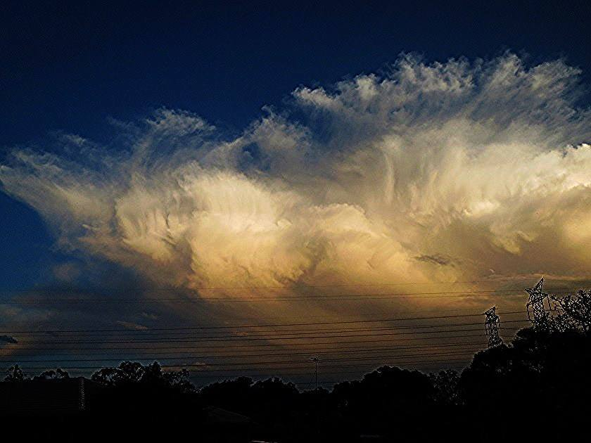 Heavily glaciated cumulonimbus clouds lit up by the setting sun after a supercell swept over and dumped large hail. Brisbane, Australia September 16th 2014.