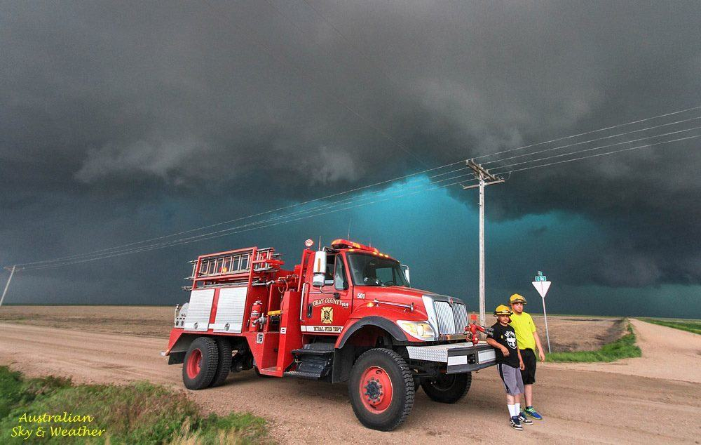 Small communities in western Kansas are supported by volunteers in storm times. Looming in the background is a tornadic supercell.....volunteers Derek & Aaron stand by and act as spotters for Gray County (Cimarron). It's amazing to see how communities band together and are fully prepared for the worst. 27th May 2015