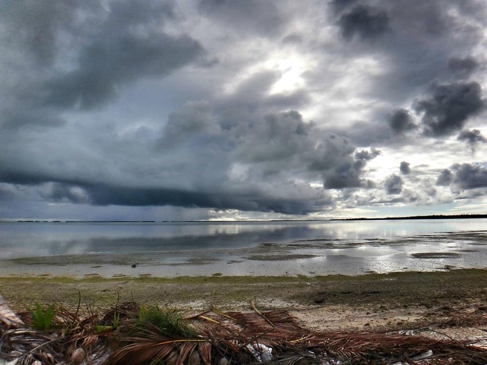Low cloud & unsettled weather rolls over the glassy lagoon of Cocos (Keeling) Islands, Indian Ocean. (2013)