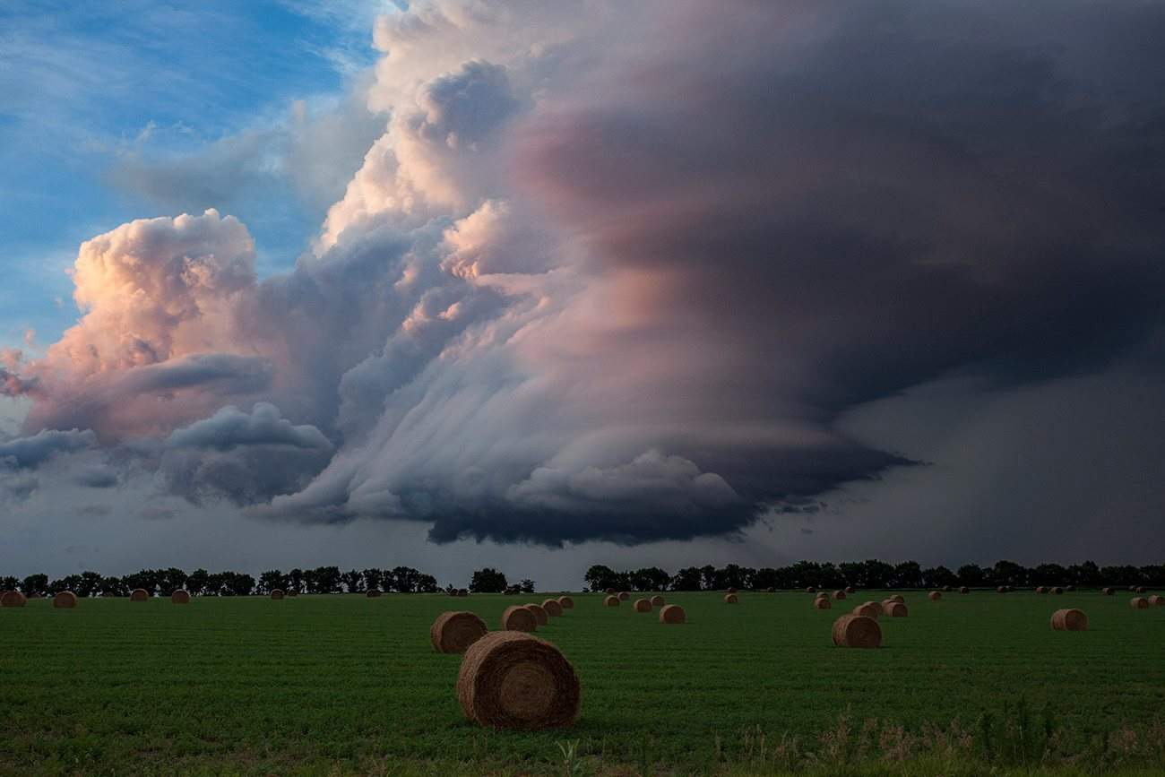 Waning supercell in the sunset. There's a time in the late evening when the light gets just right for the subject, but I had no forground. Then suddenly the scene opened up to a lush green field with hay rolls... almost too good to be true. Guide Rock, Nebraska 15 July, 2015