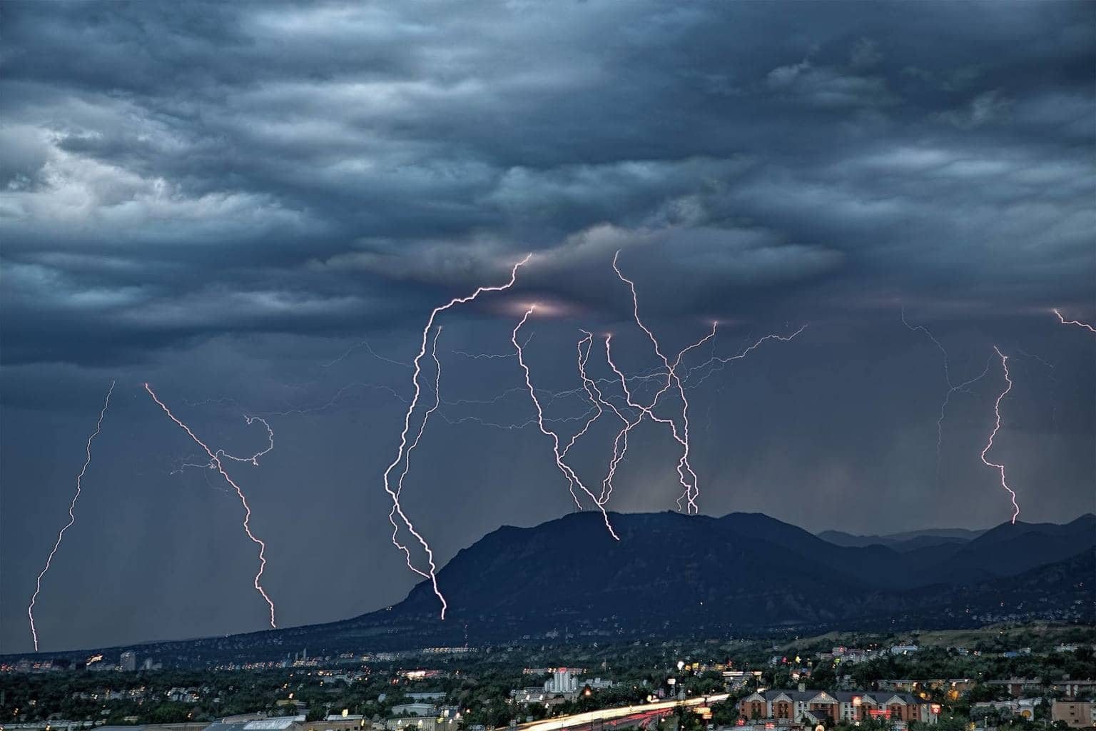 Lightning bolts over and near Cheyenne Mountain in Colorado Springs from Thursday's early evening storm. This is an 11 frame composite. 08/13/2015