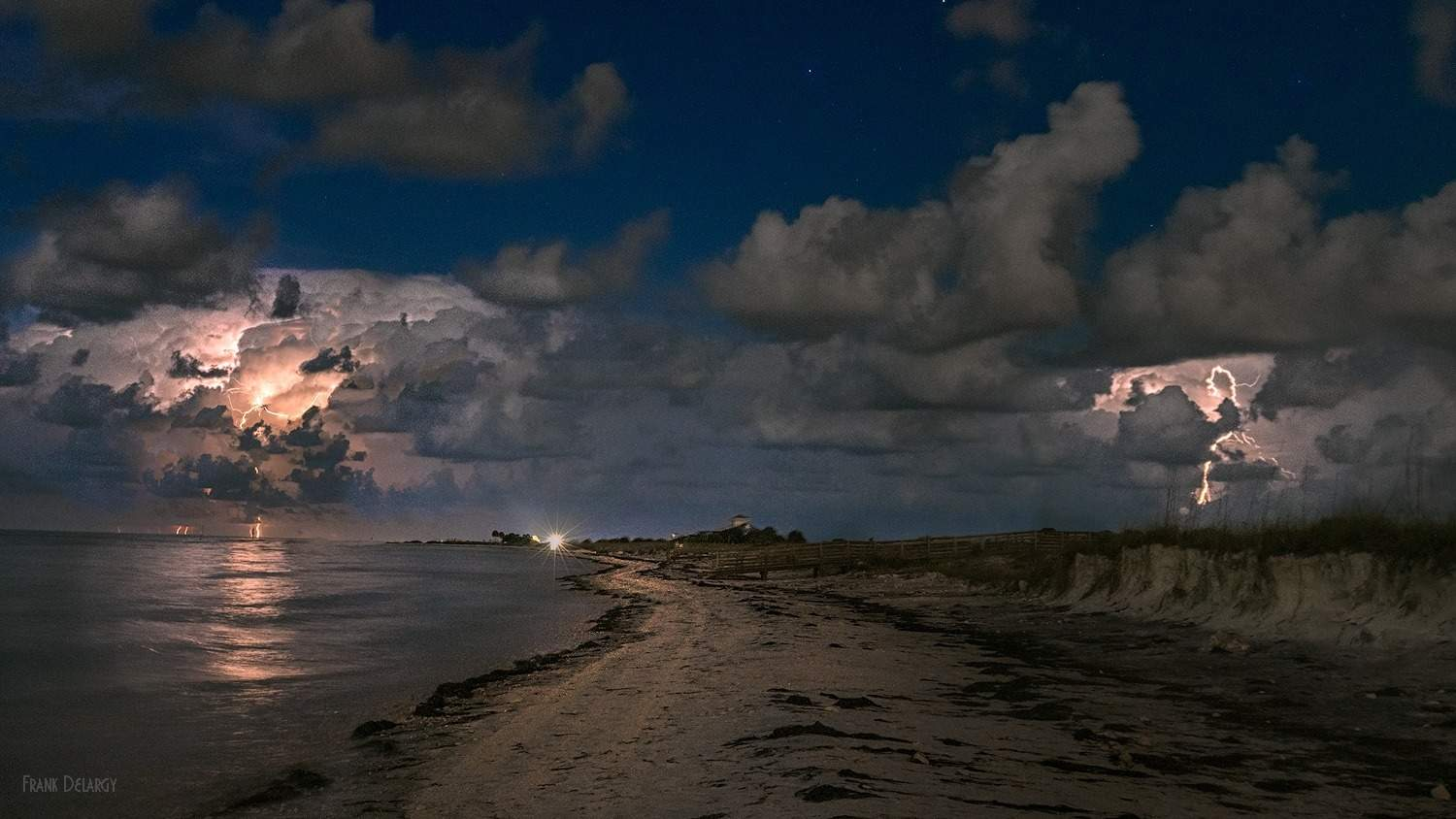 Enjoying the distant storms over the Gulf of Mexico from the beach. — at Honeymoon Island State Park.