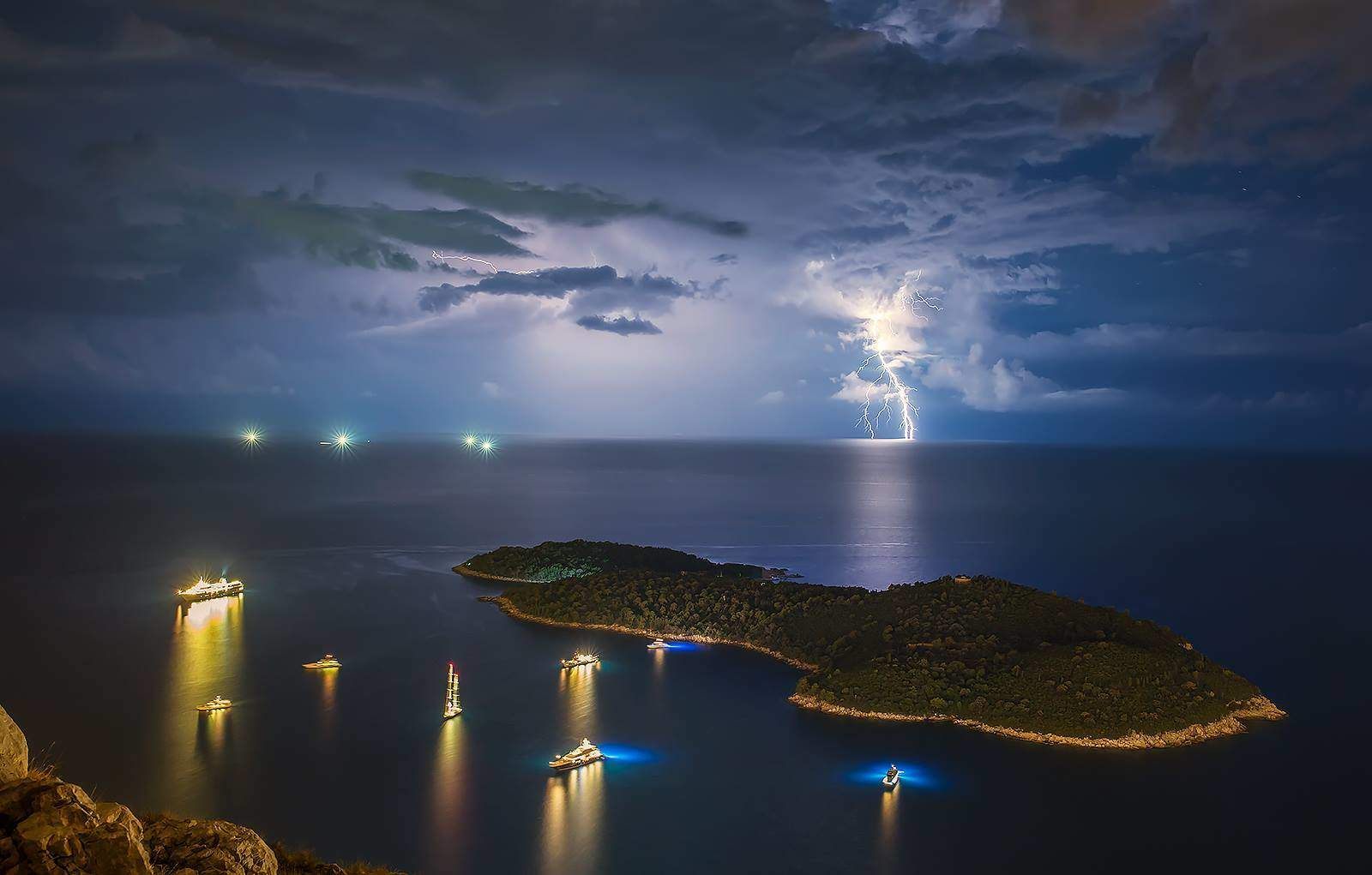 Lokrum island and isolated storm on open sea.