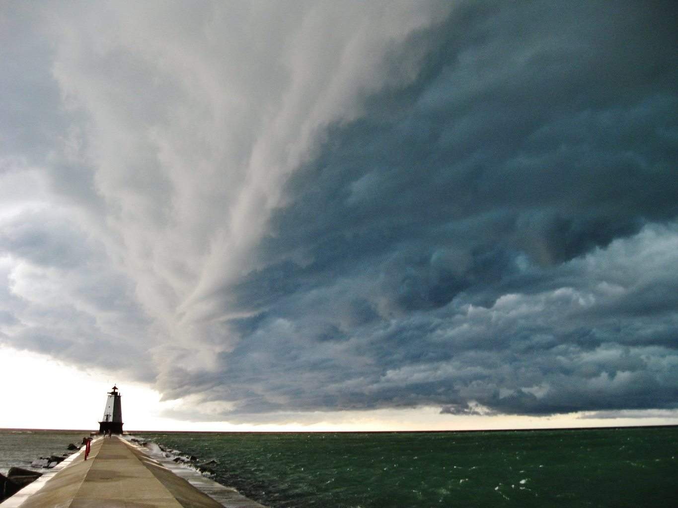 Massive storm approaches a lonely lighthouse in Ludington, MI last Sunday. Storms over water seem more raw and powerful, somehow, with spray being kicked up from the waves and the wind almost knocking me over as I took these shots!