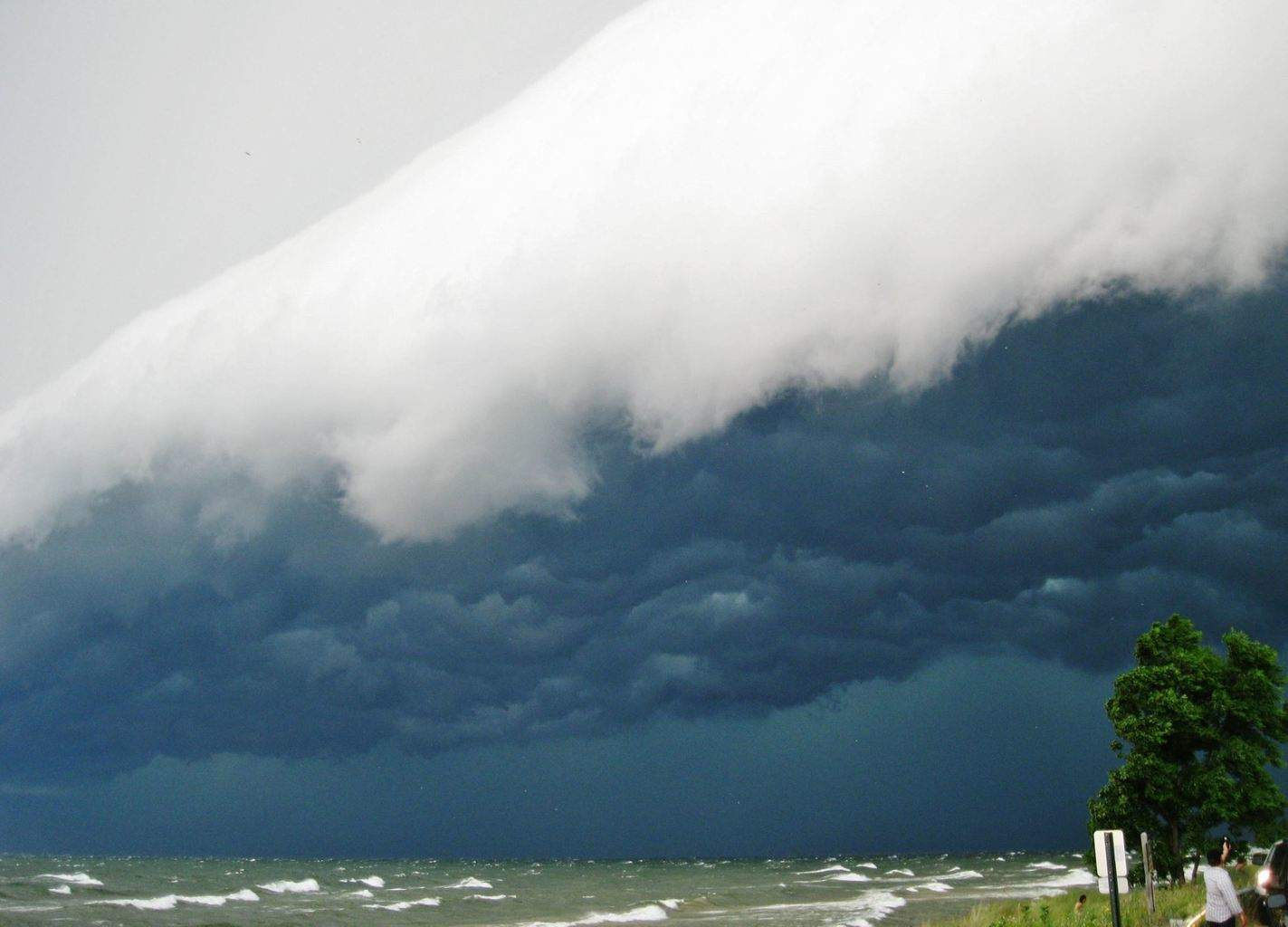 Huge storm system moving into Muskegon, MI on August 2nd. The tiny dark specks in the upper left corner are birds that were soaring along the leading edge of the gust front, like surfers riding a monstrous wave. If I had arrived at this beach just two minutes later, I would have missed this whole spectacular scene..