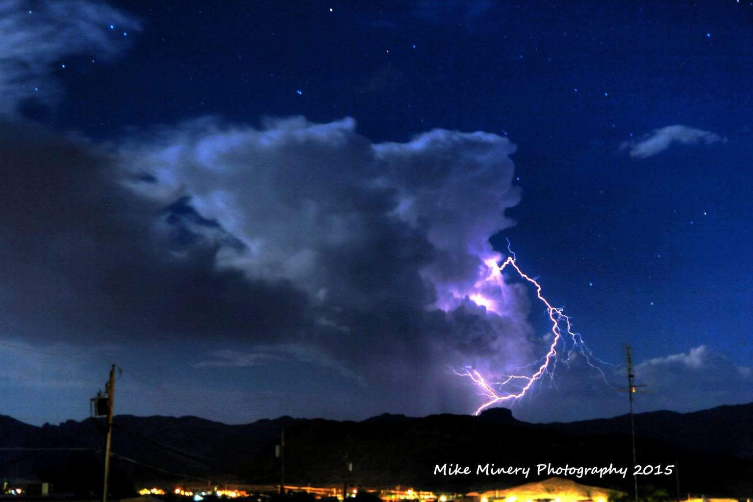 Maybe one of the most strangest lightning bolts I have ever captured. The bolt literally blew out of the side of this cumulus cloud went around it then nailed the ground. It was so cool! This is looking directly at cup cake mountain on the CA side of Lake Havasu, AZ. Photo was taken by me on the south side of town. Photo credit - Mike Minery