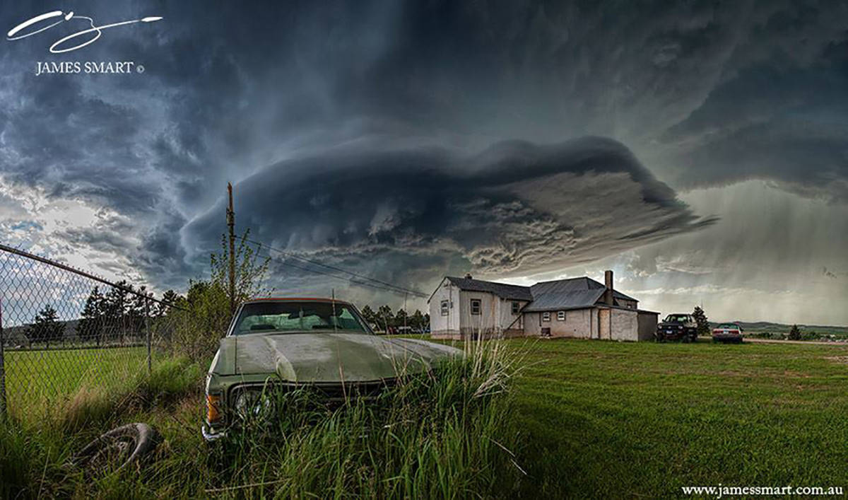 Rundown car sits in overgrown grass in the path of an incredible storm near Blackhawk, SD. 10 image panorama.