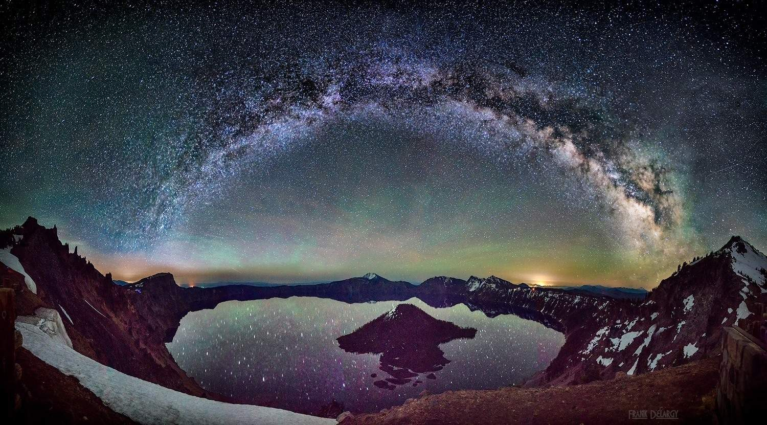 The milky way over Crater Lake in Oregon. The green and reddish colored areas just above the crater are from airglow, basically elements, mostly nitrogen and oxygen, whose electrons having been ionized by the sun during the day now recombining with their host atoms. The green and the red are from oxygen atoms that are glowing. At first I thought it might be camera noise but then I could see that the light was actually reflected in the lake. Technical: This is a panorama of 21 merged images, 3 rows of 7 vertical images each. It is impossible to imagine the scale but with my wide angle lens I was only able to get the island (Wizard Island) in one frame. This was at 3 AM on a clear night last May just as the bright moon set. The moon was so bright that you could not see the milky way until the moon set. I then had about an hour before the sky would start to lighten and the milky way would disappear again. It took about 20 minutes to take all of the exposures. Each exposure was 30 seconds at f/2.8 and ISO 1600. The lowest row was at about 20 mm and the top two rows were at 16 mm. I used a Sony A7R with a Canon 16-35mm L II lens — at Crater Lake National Park.