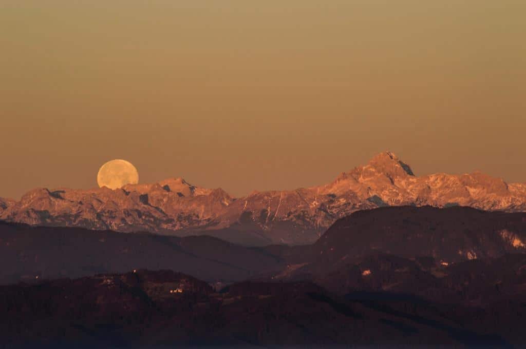 2015 Christmas full moon is setting behind the highest mountain in Slovenia, mt. Triglav, 2864m high. At the same time, the sun has just risen over the horizon behind me.