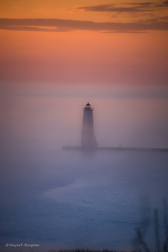 Fog rolling in from Lake Michigan at Frankfort Light House.