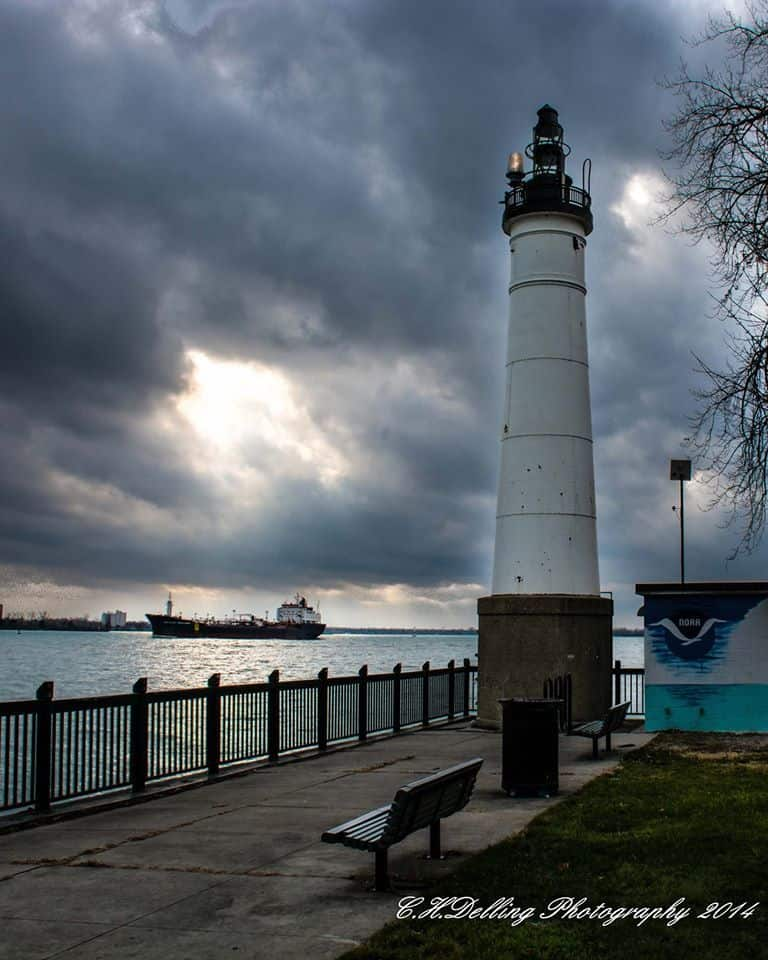 Windmill Point Lighthouse in Detroit. A hole formed in the cloud cover just in time to shine some light on a passing freighter.