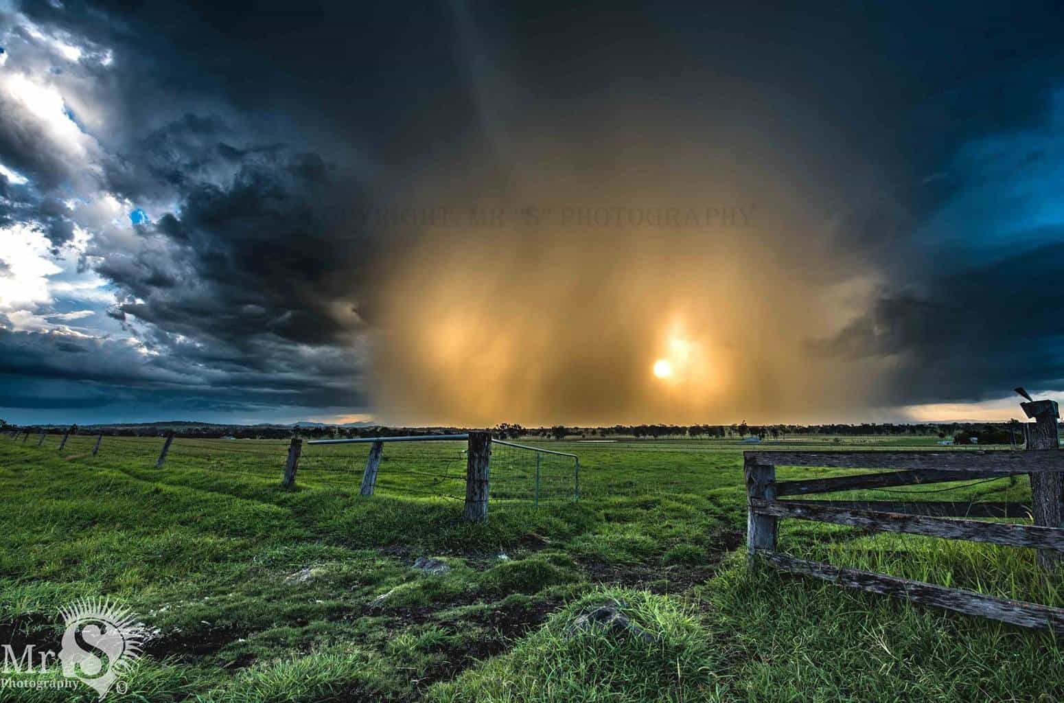 Today's Sunset at Peak Crossing in Queensland Australia was blocked by a slow moving and weak thunderstorm. It made for a really cool affect as the sun pushed through the rain core and lit it all up golden.