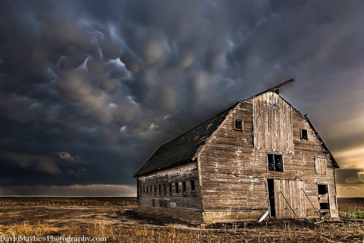 """""""Defiance"""" An old barn with its door agasp weathers another storm as mammatus clouds sneak up behind it. Near Oakley KS. May 30th 2012. You never know what you might stumble upon while storm chasing. This was post chase on my way home, I had already switched the Chase Mode light bulb from red to off!"""