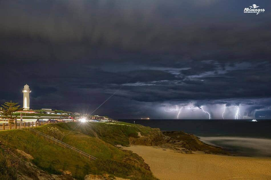 Car lights shine as cars come and go, they are all there on the headland to watch the evening lights show over the ocean. Wollongong, Australia