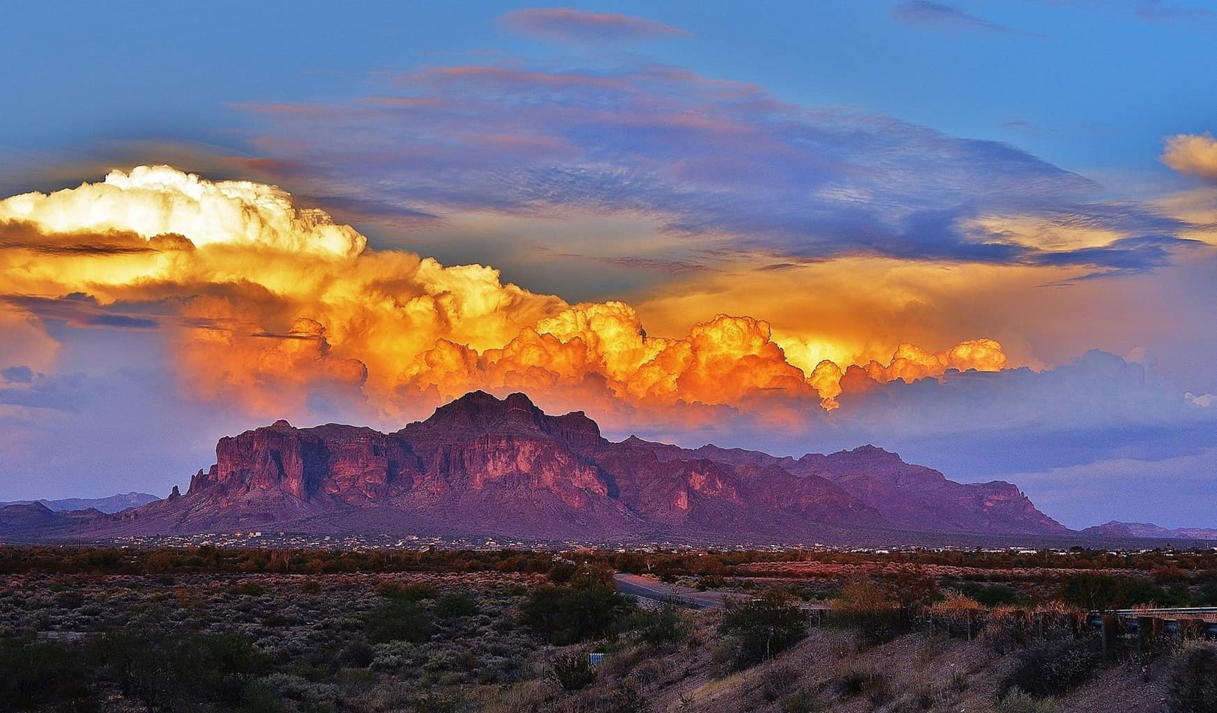 Storm brewing over The Superstitions - Apache Junction , AZ . ~ 08/31/15 The Sun was setting behind me and gave these clouds their golden glow for a few minutes .