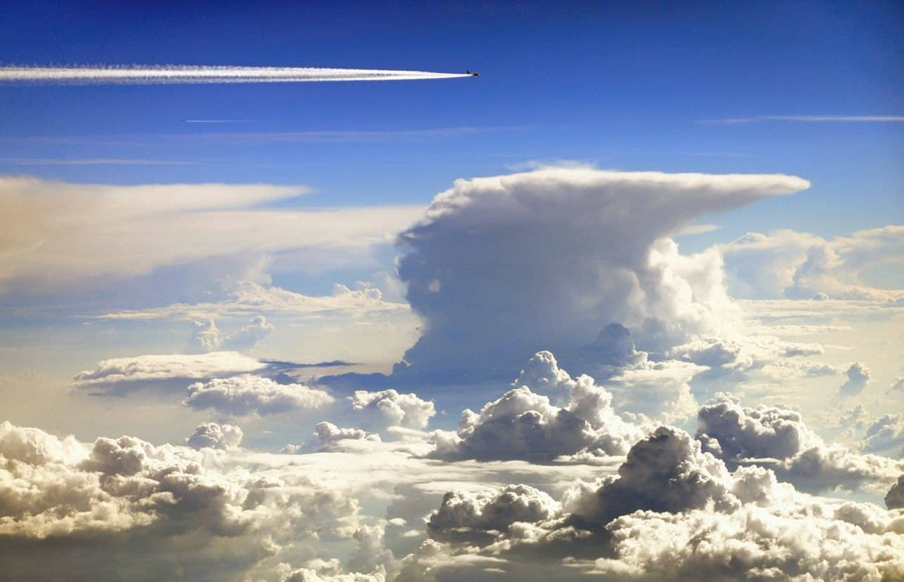 Classic anvil shaped thunderstorm viewed from airplane window seat. Notice the big ass contrail formed by a nearby passing plane. By the way, am i the only one seeing frogs and gators heads in the surrounding low cumulus clouds?