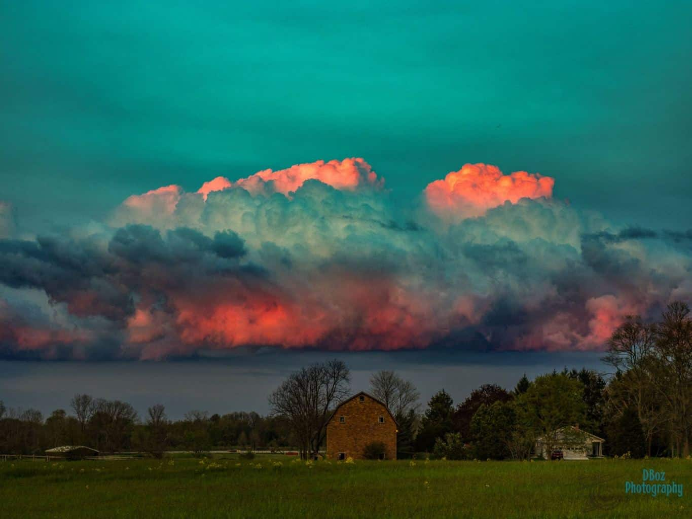 One big fluffy cloud is illuminated by the setting sun on May 7, 2016 in Rives Junction, Michigan. It seemed to settle on this barn for the evening.