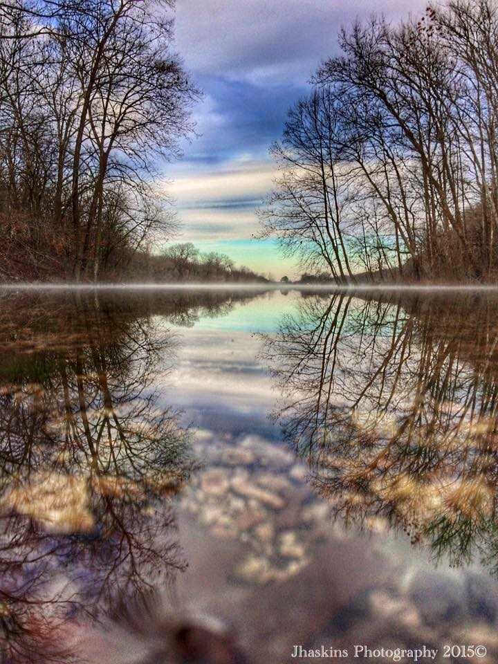 Cloudy skies, layer of fog in the distance riding the water that was so calm it made an awesome mirror effect!! Hint: Look at the photo upside down as well ;) Crystal Lake, Decatur, AR 2015