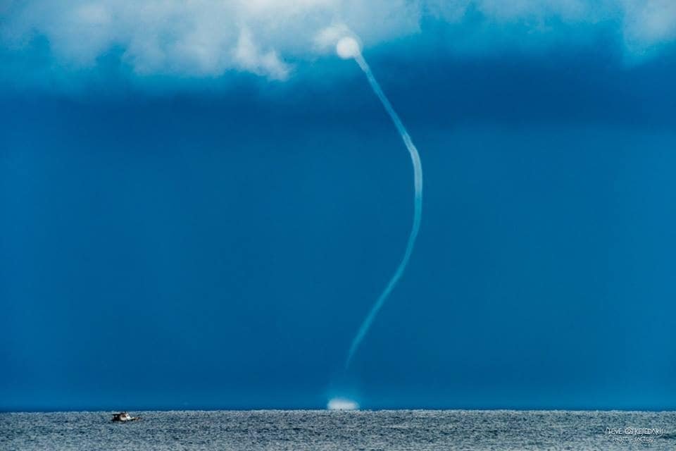 Twisting waters.....!!! A fisherman drives his boat next to a waterspout off of Rhodes island Greece