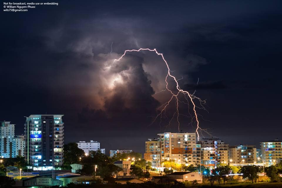 Distant storms light up the city line in Darwin, Australia.