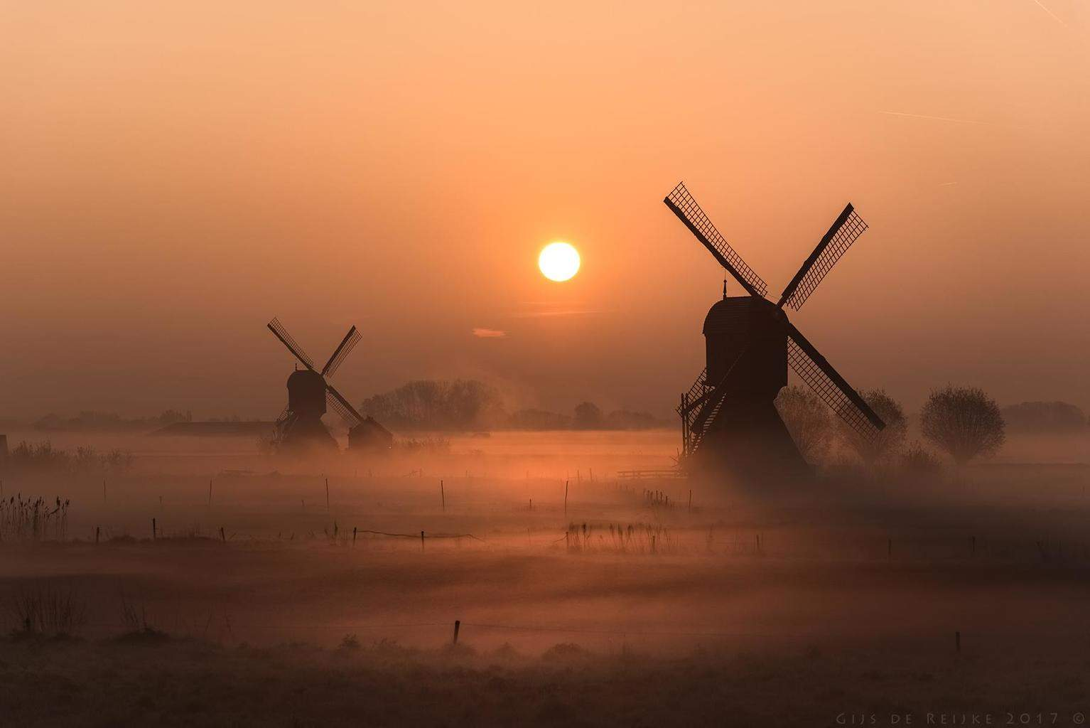 A golden sunrise over two windmills in the Land of Heusden and Altena, the Netherlands, this morning.