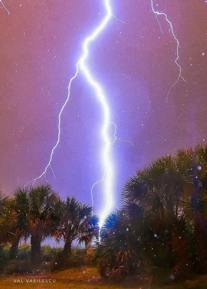 """Sarasota, Florida  With our Florida storm season rapidly approaching in just a couple of weeks, I wanted to share with you all my favorite photo of all time that I've captured. Last summer, I was on the beach taking photos of bolts about ten miles out over the Gulf of Mexico. While doing this, a thunderstorm blew up right over me in five minutes. A bright flash appeared behind me so I got into a friend's car and we drove down the beach to a place that had a little bit of cover. I set up my camera and then the sky opened up with extremely heavy tropical rain. I was surrounded by a puddle of water and being hit by rain all around. In an instant, this massive bolt hit right in front of me! I saw a blinding flash and instantly heard the explosive, deafening sound of thunder. I'm so happy that my camera was running and that it was good enough to capture this close-proximity bolt in perfect detail. I love how it lit up the palm trees, because it makes it a true Florida photograph. I also like how the raindrops are being illuminated by the bolt. It's also so fascinating to see the feelers trying to find something or someone to strike! Florida is the most active lightning state in the USA and also the deadliest. Many people here die when it's a clear day. Lightning can travel many miles away from a storm cloud, so people will go walk their dog or walk to their car thinking they're safe, but Florida storm clouds are fueled by incredible energy and moisture. As they explode to over five miles up in the atmosphere, a bolt that reaches out from that high will seek out a target well over 10-25 miles away! I hear it every year that someone saw a clear blue sky, went outside and a bolt """"out of the blue"""" killed them. If you're outside and you hear thunder, you have to assume that you're in the strike zone. You should all be using a radar app and always keep an eye on it when you're outside. I have spent years getting close to lightning and it can do anything it wants. It will seek """