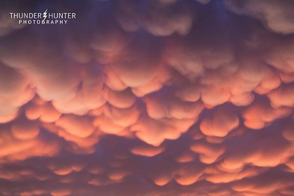 JUST HANGING AROUND...... These mammatus clouds were coloured in a way that I had never seen before. Adjacent pockets were clearly hanging down lower and were shades of white while others were higher and were shades of orange,pink and red. Really cool for a few minutes in Oklahoma - May 18th 2017.