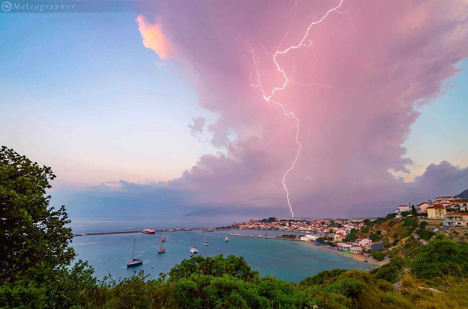 Photogenic cell spewing a lightning bolt above Pythagoreio village in Samos island, Greece during sunrise.