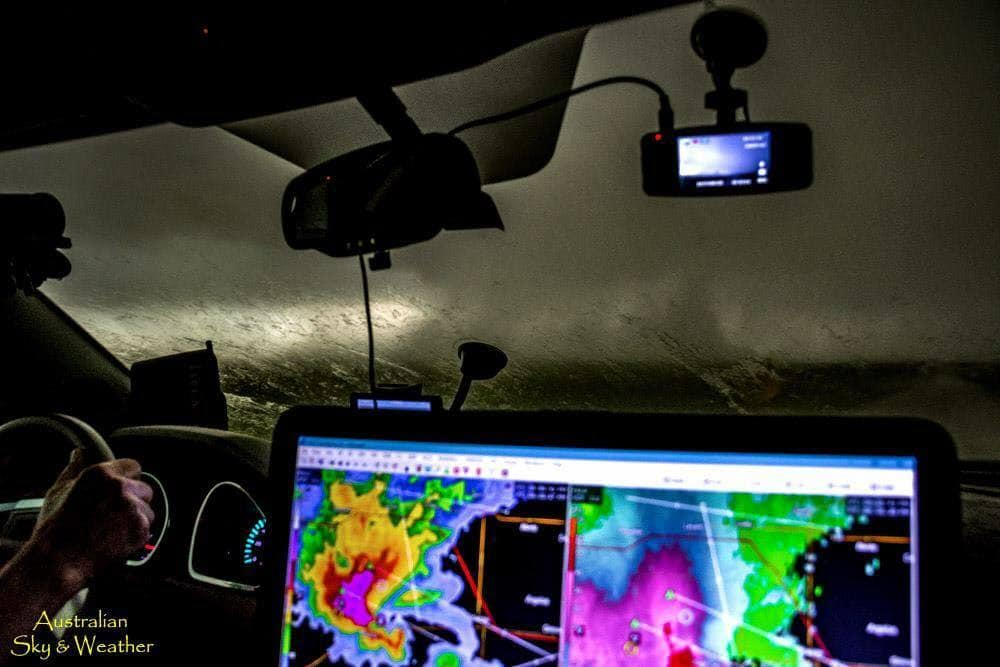 A chaser's windshield view as we approach a broad and churning mesocyclone. The radar image shows the storm with a prominent hook and a strong couplet. South of Oakley, KS 25th May 2017