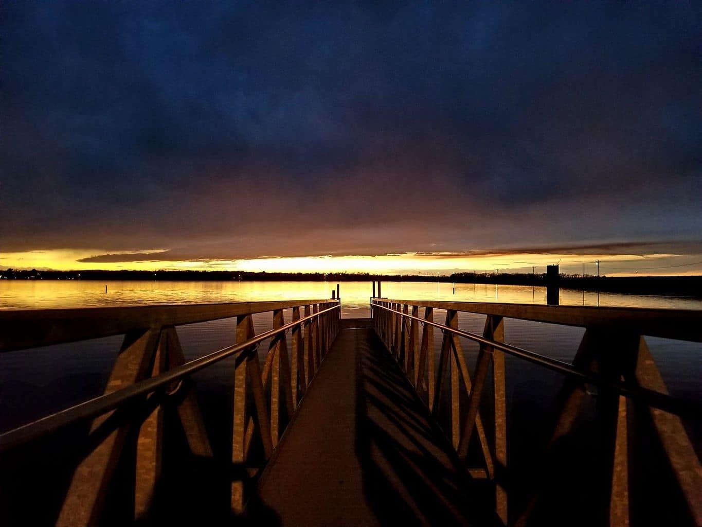 Sun setting with rain clouds over Shawnee Lake, Oklahoma.