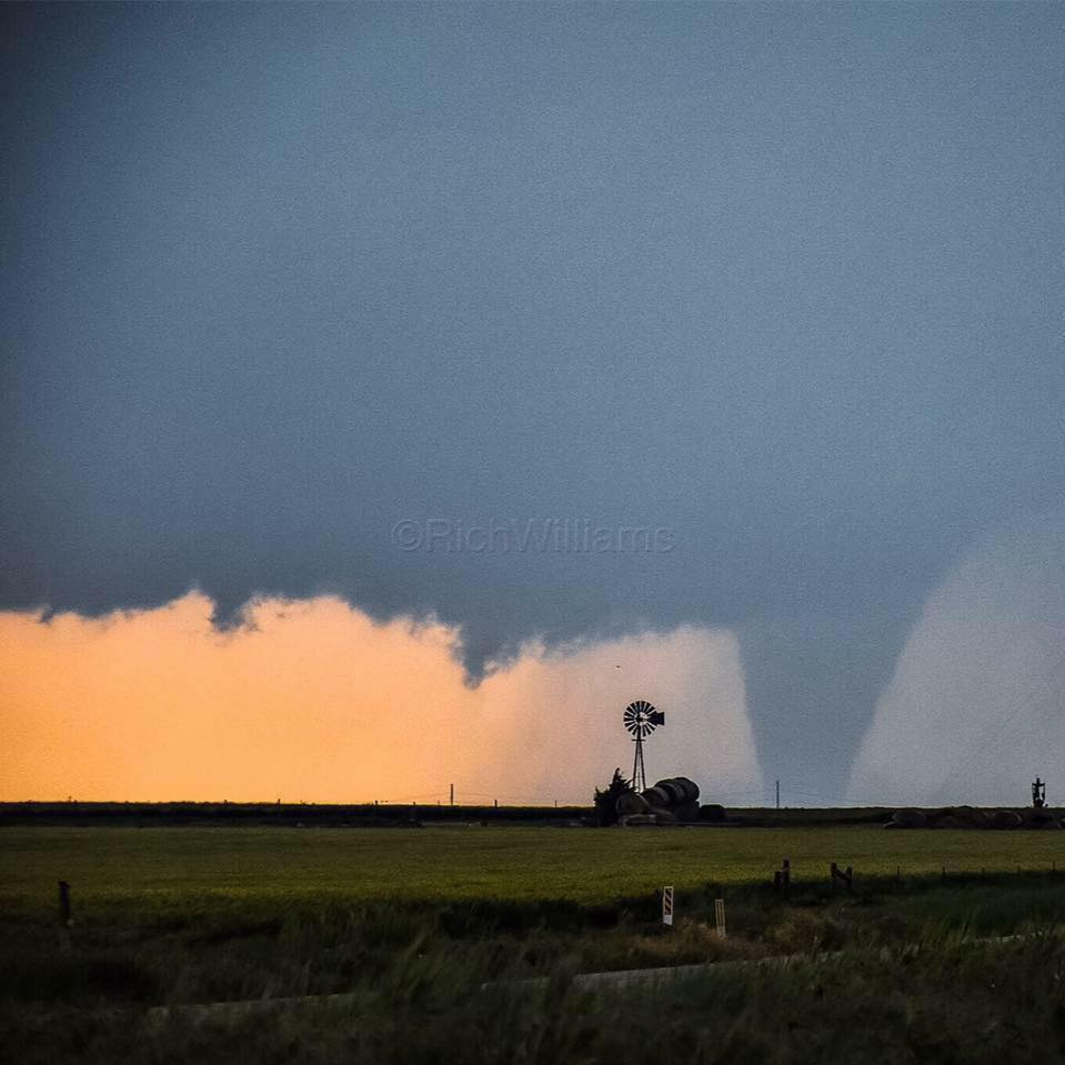 A KANSAS CLASSIC!! The sun creating an orange glow, a Kansas windmill, and a large stovepipe Tornado!!