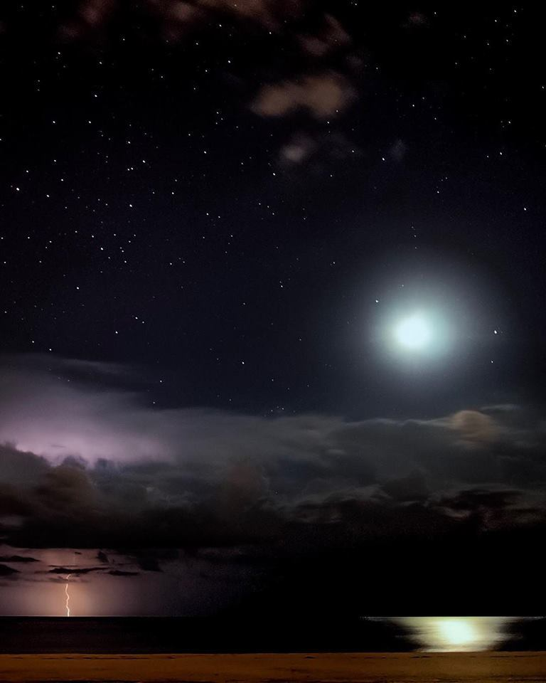 """Sarasota, Florida This was one of my first attempts at capturing lightning. It is a single time exposure. The moon will soon set over the Gulf but not before a thunderstorm drops a few bolts below. This photo has always been very symbolic of the dual nature we see so much in the universe. On the right, the stillness of the Gulf is seen as the moonlight shimmers across the water, the light stopping at the base of the sand. On the left is a storm dangerous to anyone caught underneath its fury. The towering clouds are lit up both by the setting moon and the lightning, revealing the complex structure of a Florida summer storm. Above it all, the stars blanket the sky; the ultimate appearance of calmness, an ending to a captivating poem. The stars watch over us day and night, on happy mornings and stormy nights, they are ever present. Another inspiration behind this photo is a quote by the father of modern painting, Paul Cézanne, """"Art is a harmony running parallel to nature."""" He boldly expresses that the purpose of art isn't always to imitate nature, but to dwell in its own eternal beauty alongside nature. I picture art and nature being two butterflies flying across a meadow, each butterfly on its own destiny, each with a different yet stunning array of colors, but both possessing priceless value."""