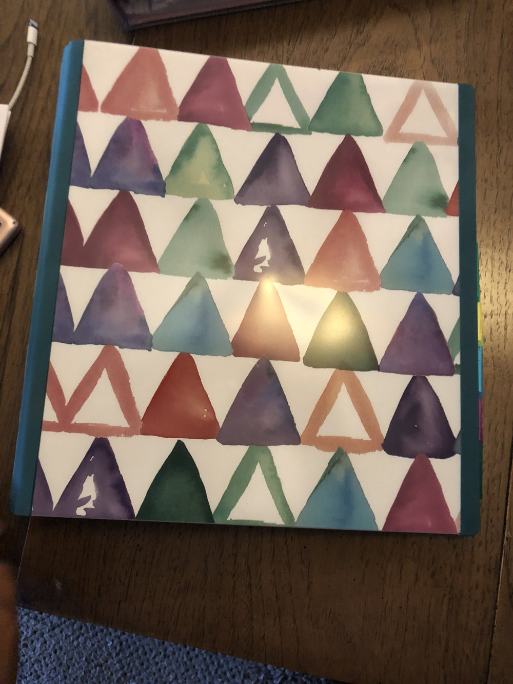Caption: I purchased this binder Staples. It has the capacity to hold 400 sheets of paper, which should carry me for a long time before I need to add a second binder. Most Office Supply stores have really beautiful options. I also like this binder because it has a lot of symbolism with the triangle. It is the elemental symbol for fire. When turned upside down it becomes the symbol for water. The colors represent fire and the upside down triangles (the white space) represents water. Triangles are also the strongest shape.