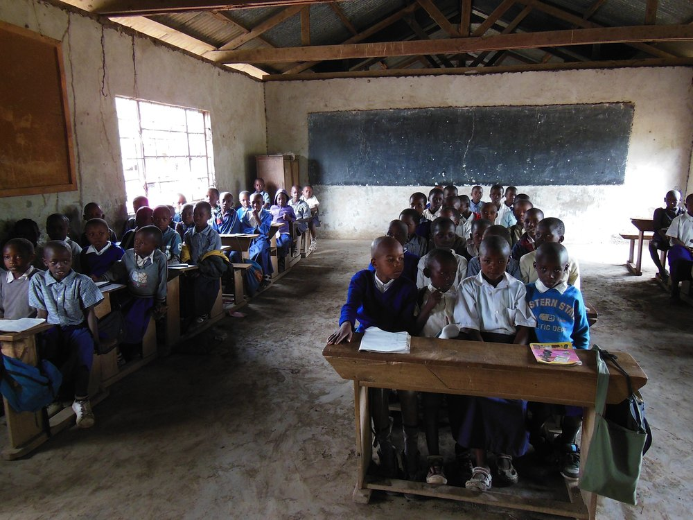 A lot of African children stay in one classroom and ready to take the class.