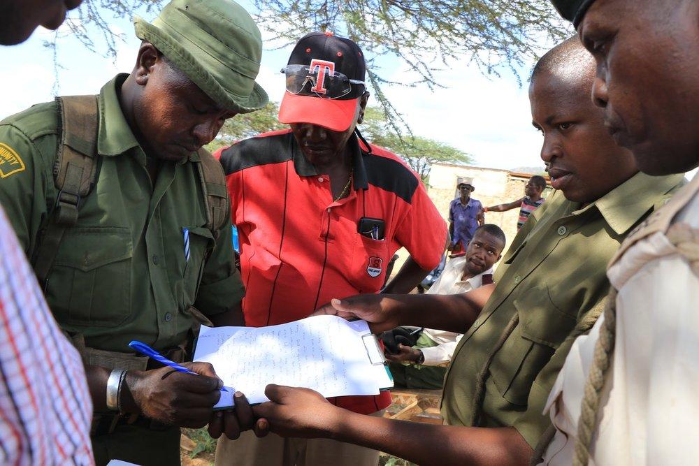 Diwani Parkusaa signs confirmation of receipt, witnessed by Waso Wwest chief,Kaward Lekalkuli, and Archers Post OCS Simon Gitau.