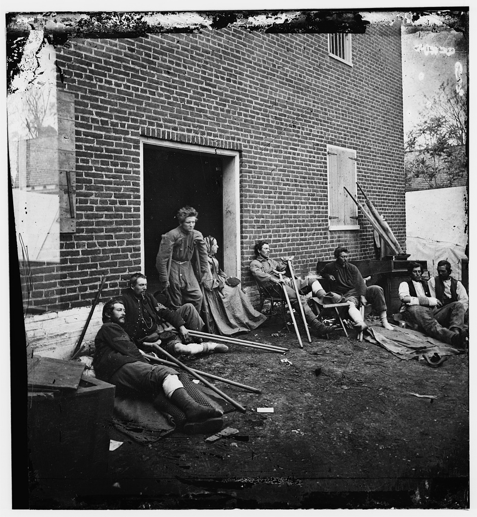 Soldiers wounded at Fredericksburg and being looked after by the woman you see sitting in the doorway, volunteer nurse Abby Gibbons from New York.    Photograph taken by James Gardner. Courtesy of the Library of Congress.