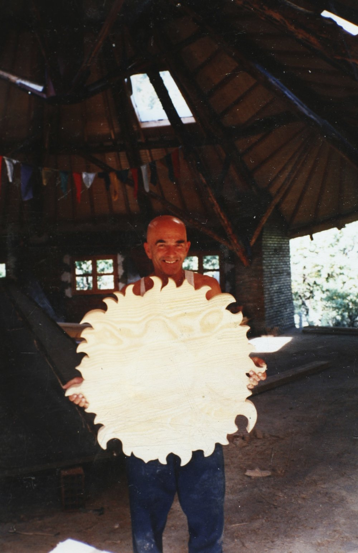 Philippe sujetando un sol de madera dentro de la sala circular en construcción.