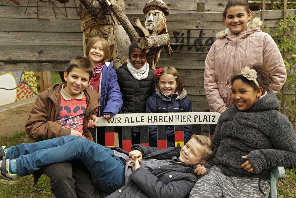 """Bild aus dem Programm CHILDREN Entdecker (Kinderarmut): Kinder unterschiedlicher Herkunft sitzen auf einer Bank mit der Aufschrift """"Wir alle haben hier Platz"""""""