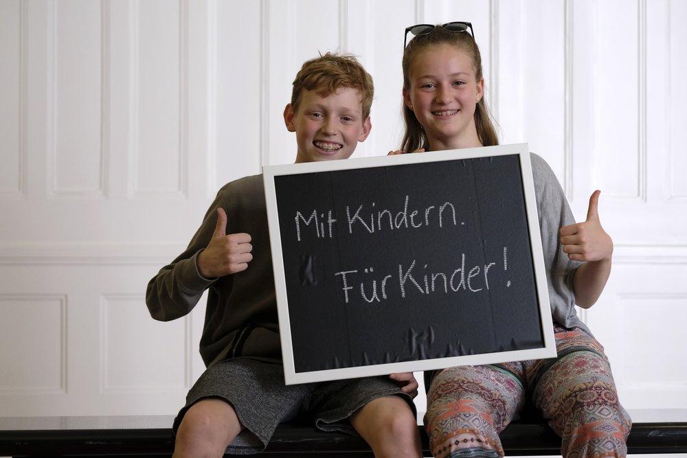 """Bild vom CHILDREN Kinderbeirat (Partizipation): Junge und Mädchen halten ein  hoch, auf dem steht """"Mit Kindern. Für Kinder!"""", beide halten den Daumen nach oben"""