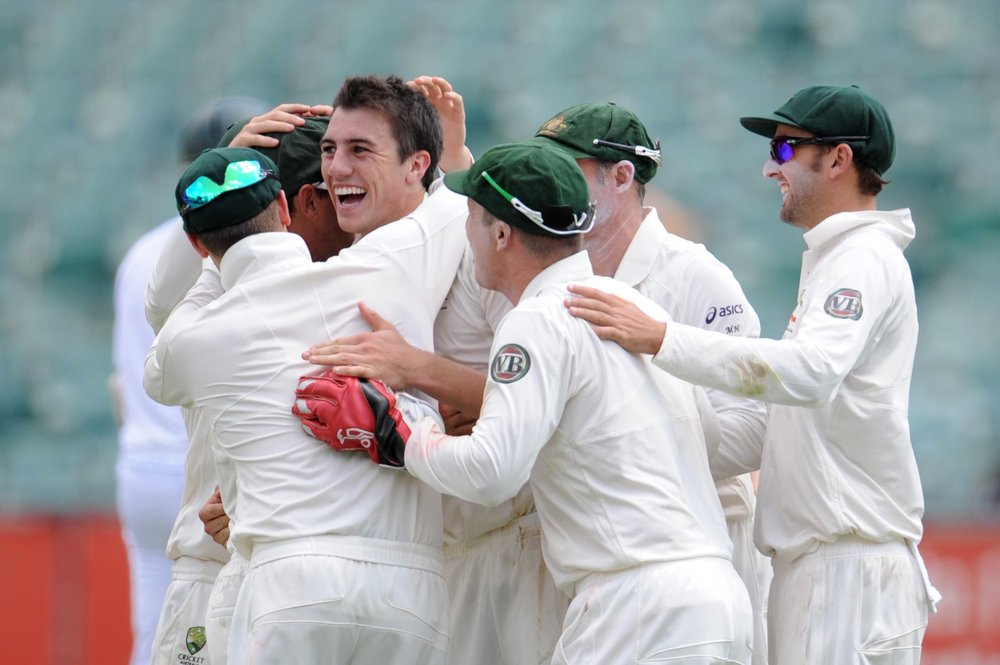 Patrick Cummins celebrates his 1st test wicket of Hashim Amla of South Africa with his team mates during day 1 of the 2nd Sunfoil Series Test match between South Africa and Australia