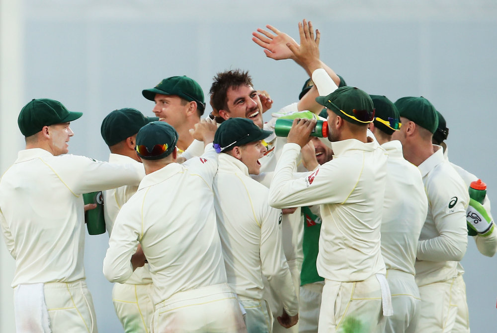 Pat Cummins celebrates with team mates after taking the wicket of Joe Root of England during day one of the First Test Match of the 2017/18 Ashes Series between Australia and England at The Gabba