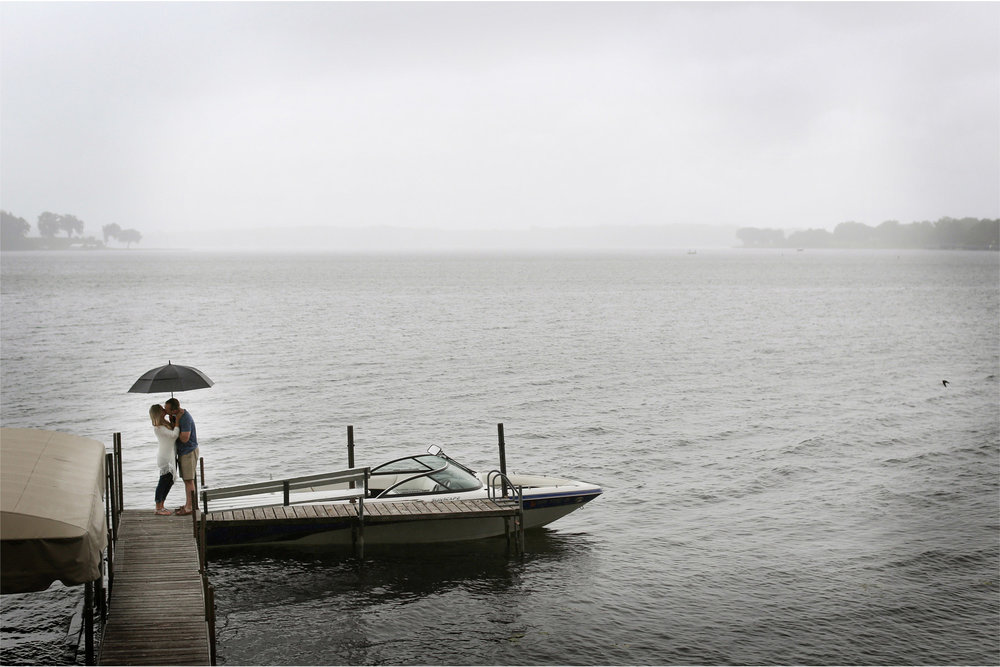 06-Wayzata-Minnesota-Engagement-Photographer-by-Andrew-Vick-Photography-Summer-Lake-Minnetonka-Kiss-Rain-Umbrella-Speed-Boat-Ashley-&-Kasey.jpg